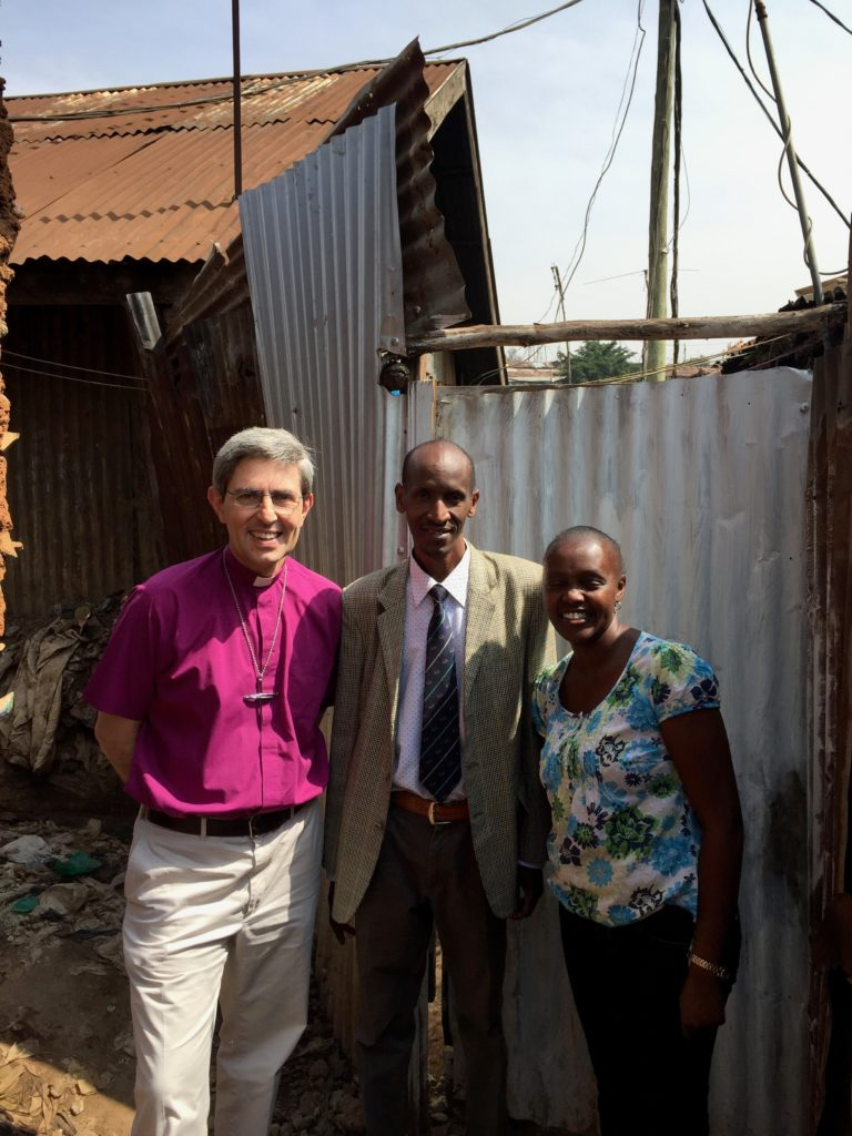 Bishop Tim, Danson Mwangi of the Church Army, and Nancy Njagi, Director, Centre for Urban Mission, outside the first Anglican Church in Kibera